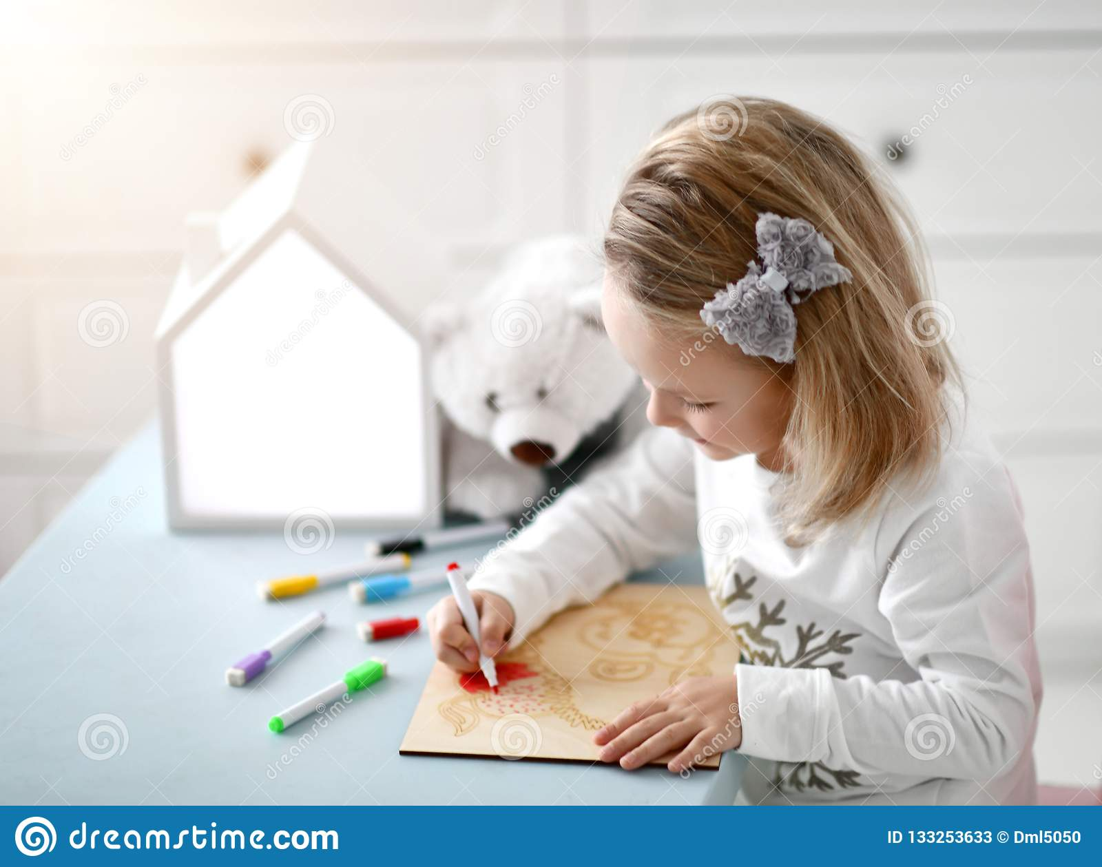Happy child baby kid girl kindergarten drawing education with colorful markers at interior room