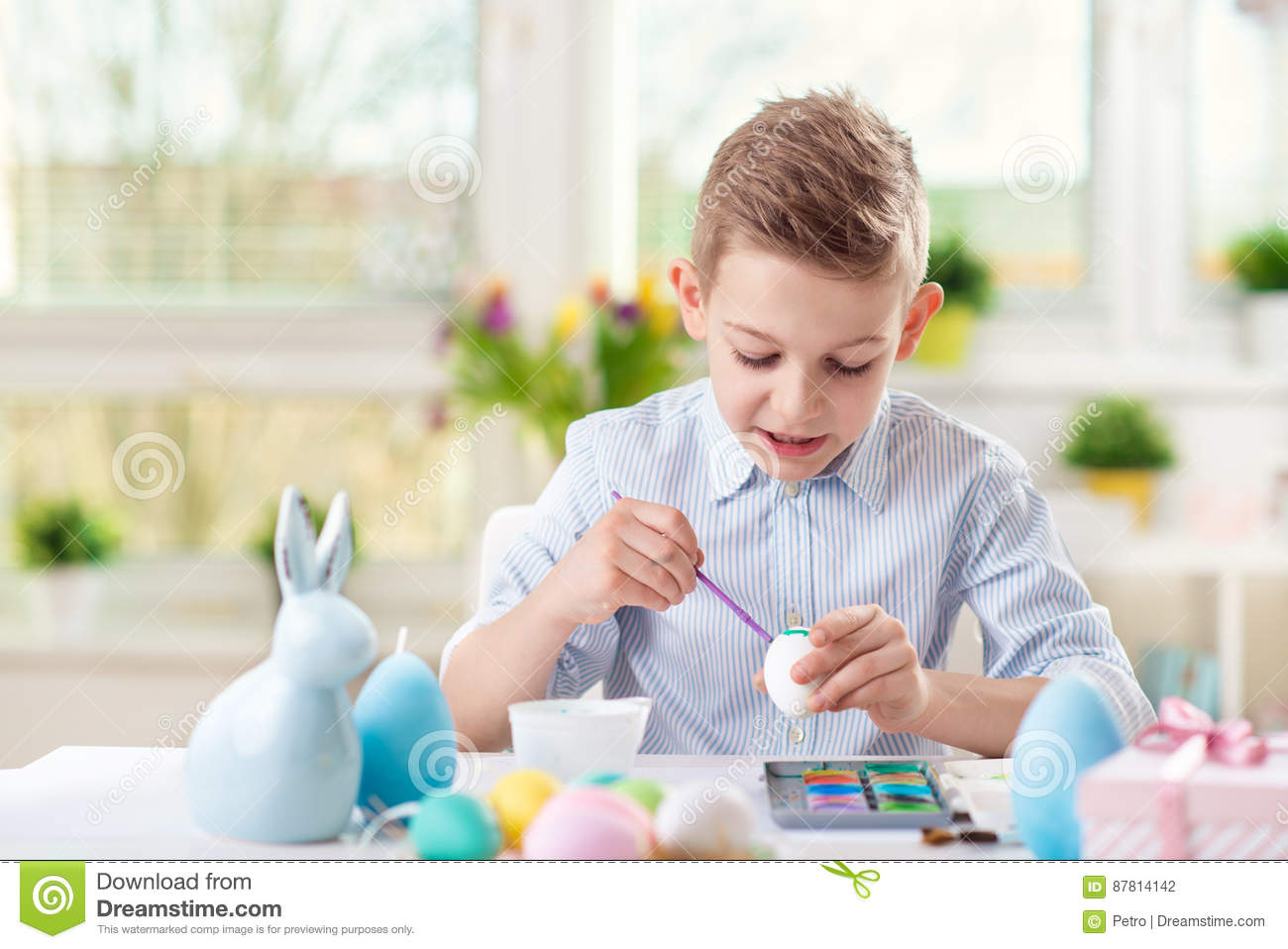 Happy child boy having fun during painting eggs for easter in sp