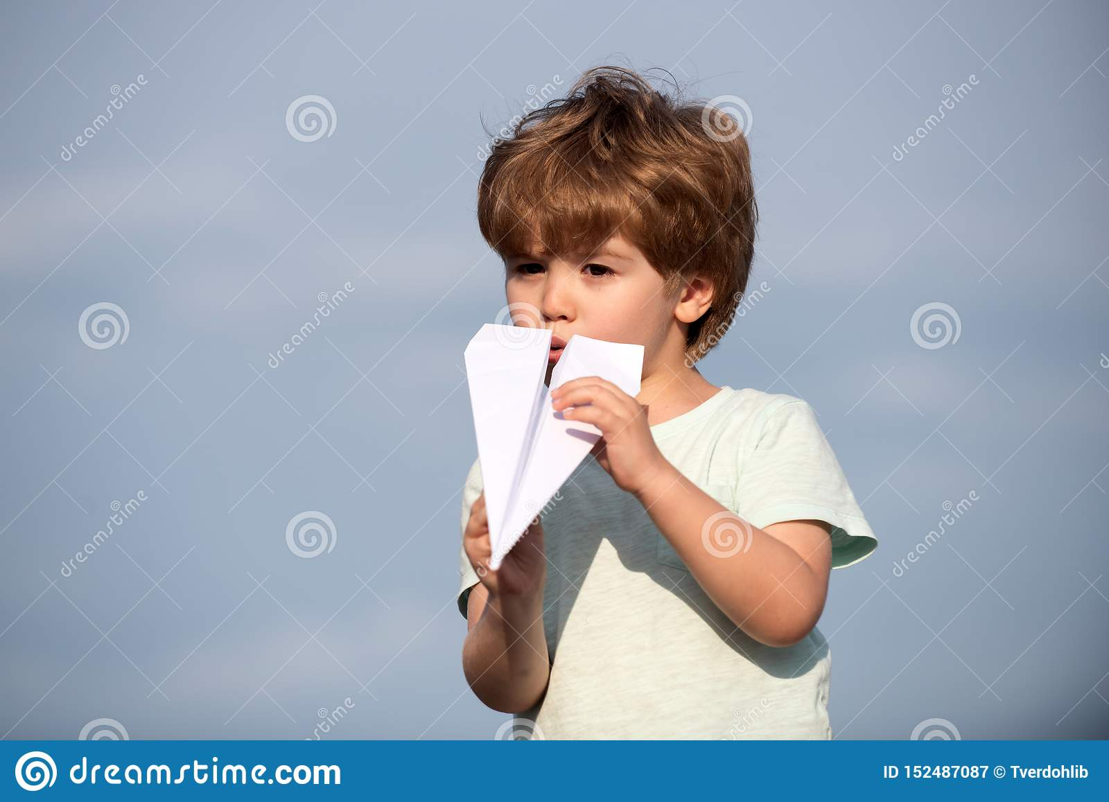 Happy child. Cute boy with paper aipplene. Happy kid on summer sky - dream of flying concept. Family travel and vacation