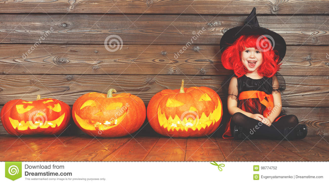 Happy child girl in costume witch for Halloween with pumpkins