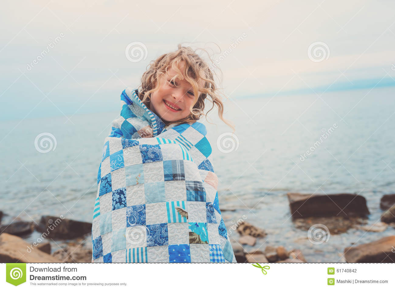 Happy child girl covered in quilt blanket, cozy summer holidays on seaside
