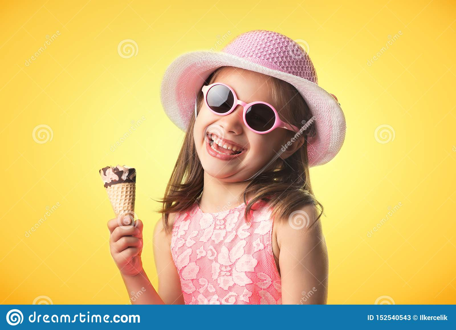 Happy Child Girl Eating Ice Cream in Summer