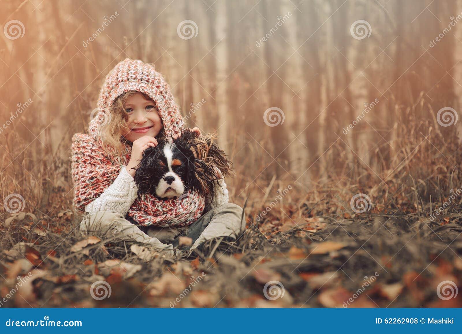 Happy child girl with her spaniel dog on cozy warm autumn walk