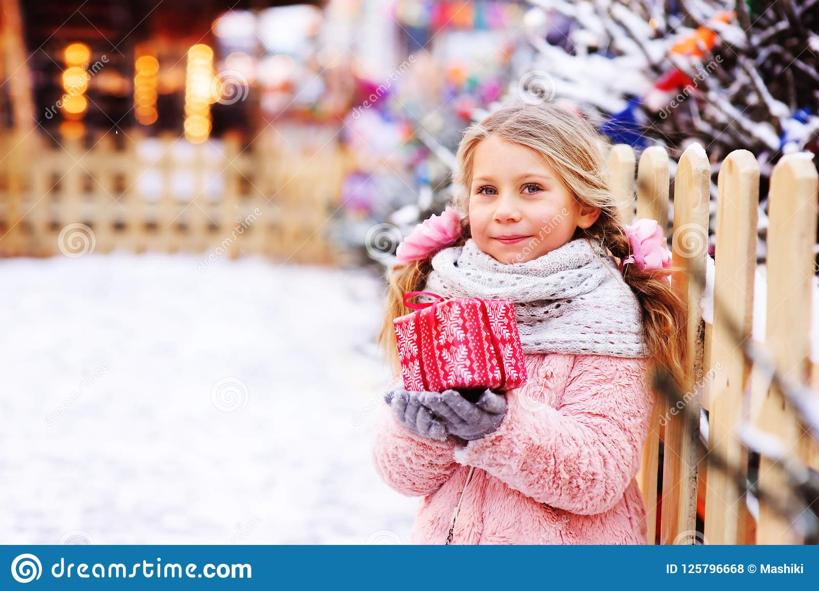 happy child girl holding christmas gift outdoor on the walk in snowy winter city