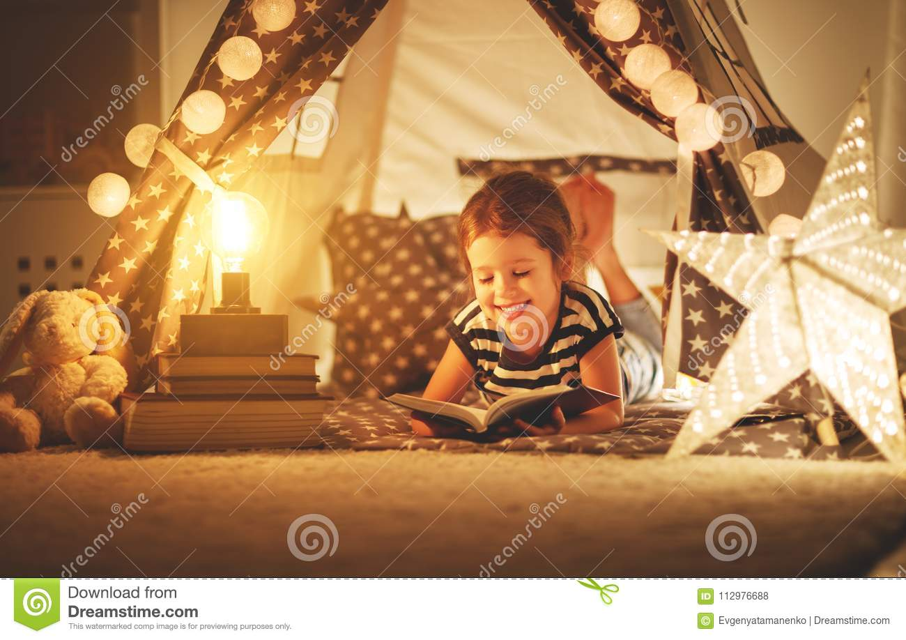 Happy child girl laughing and reading book in dark in tent at ho