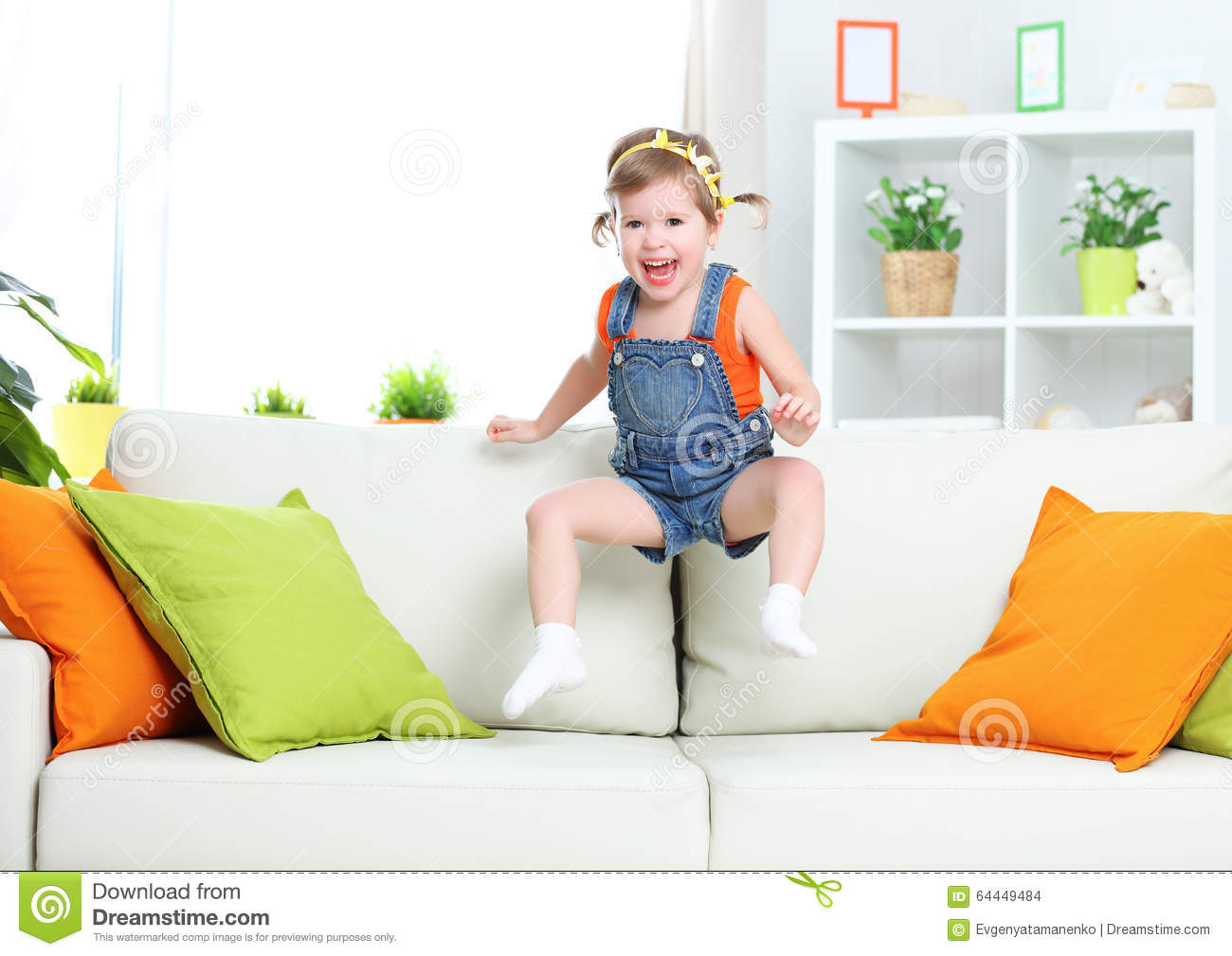 Happy child girl playing and jumping on couch at home