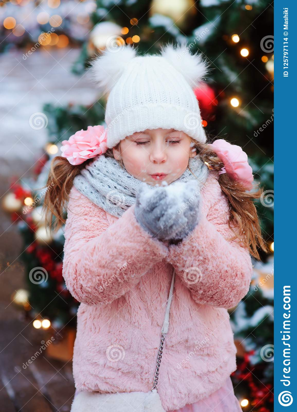happy child girl playing outdoor on the walk in snowy winter city decorated for new year holidays
