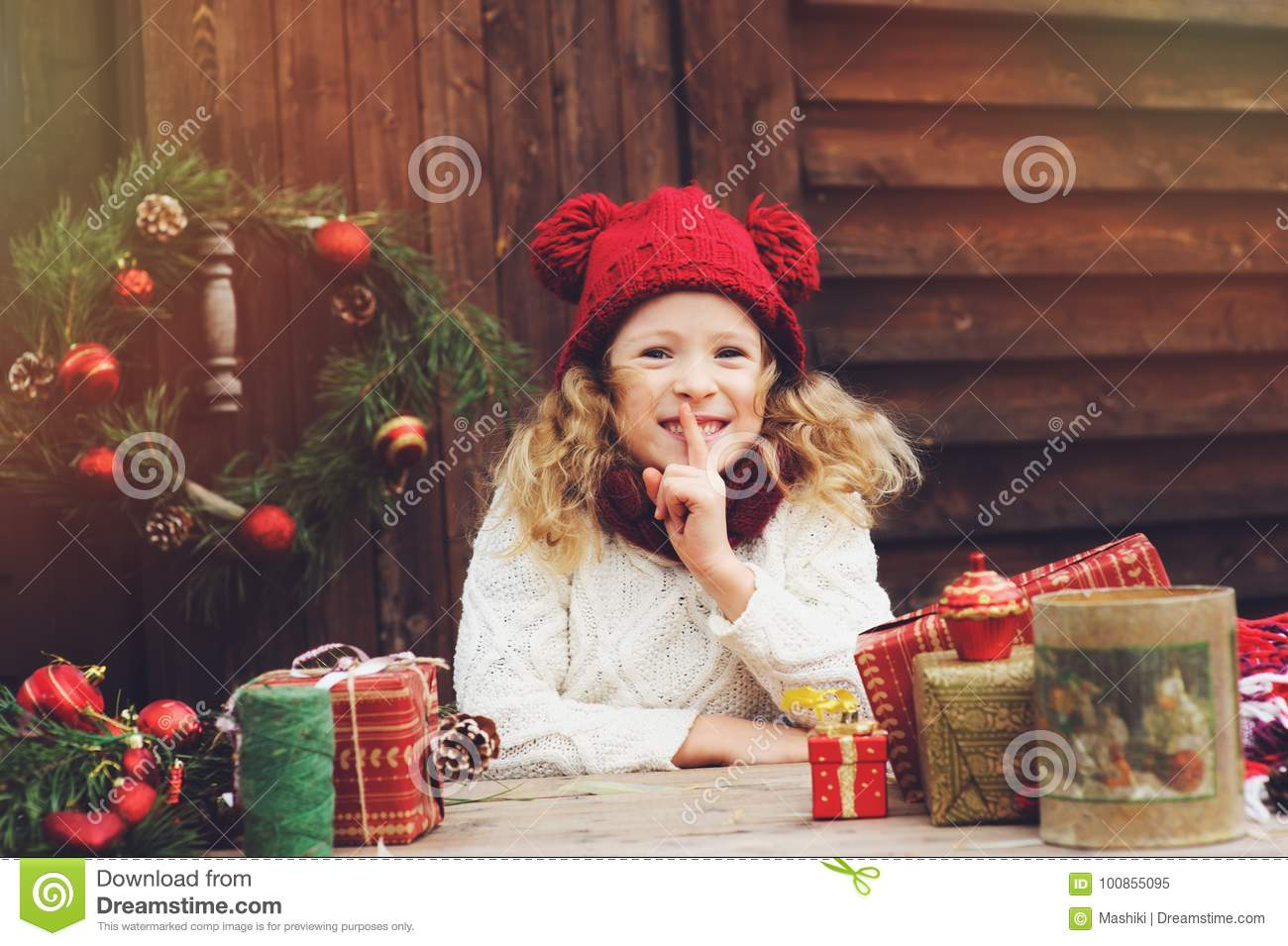 Happy child girl in red hat and scarf wrapping Christmas gifts at cozy country house, decorated for New Year and Christmas