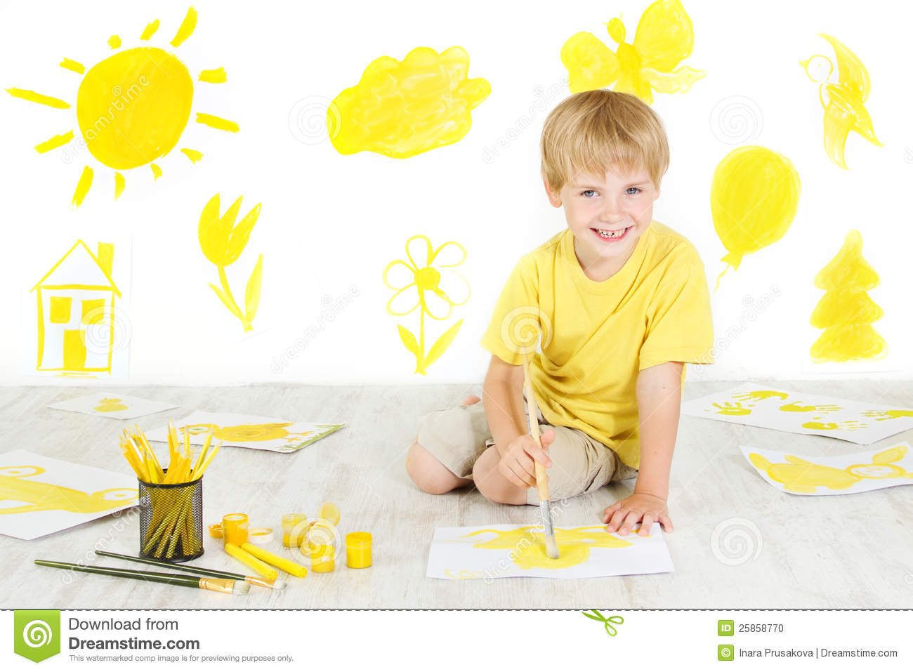 Happy Child Painting With Yellow Color Brush Stock Photo
