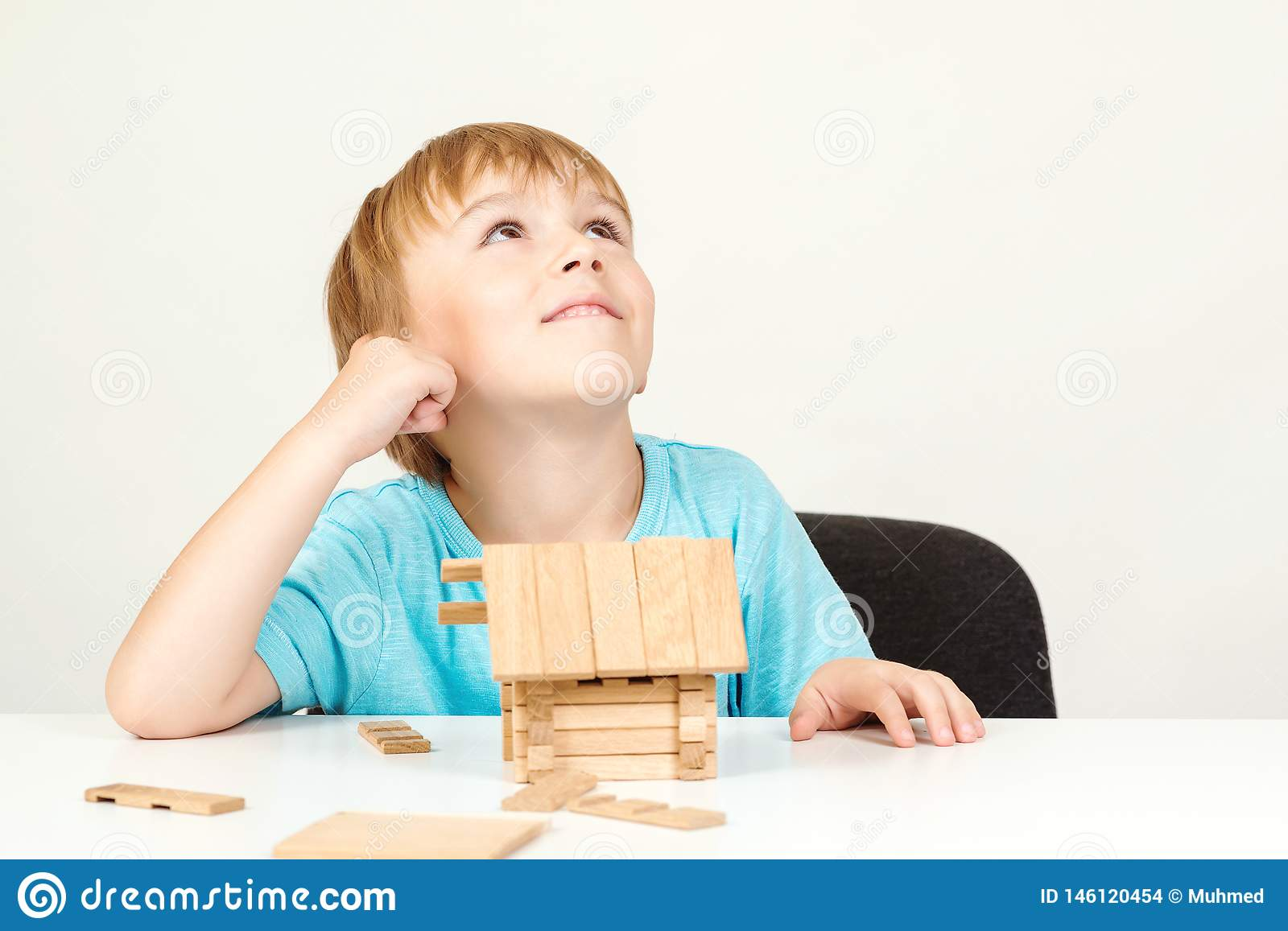 Happy child playing and building wooden home. Childhood dreams. Little boy builds his dream house. Happy life, house or mortgage
