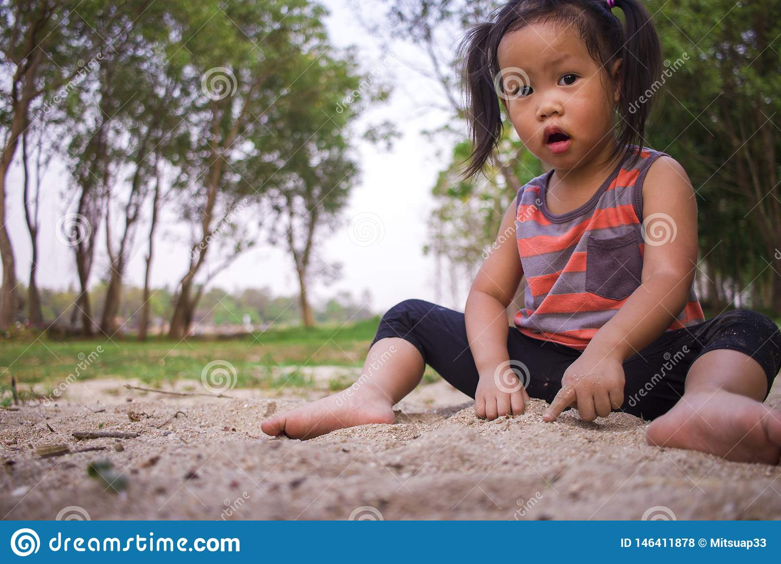 Happy child playing with sand, Funny Asian family in a park