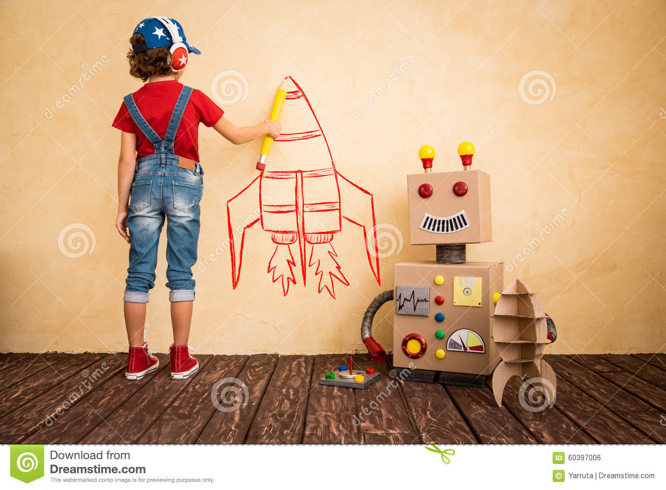 Happy child playing with toy robot