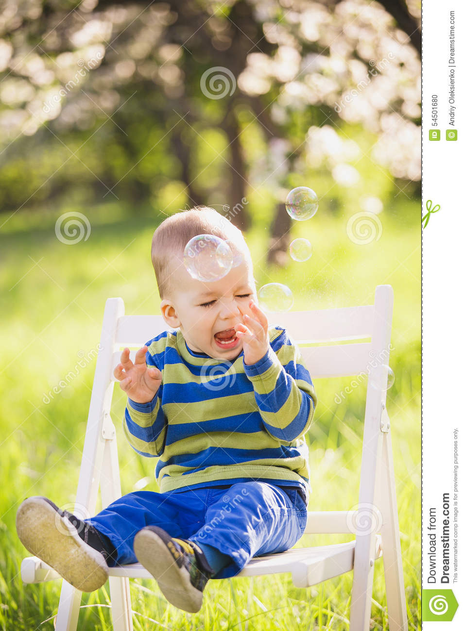 Happy child. Portrait of little boy playing with bubbles