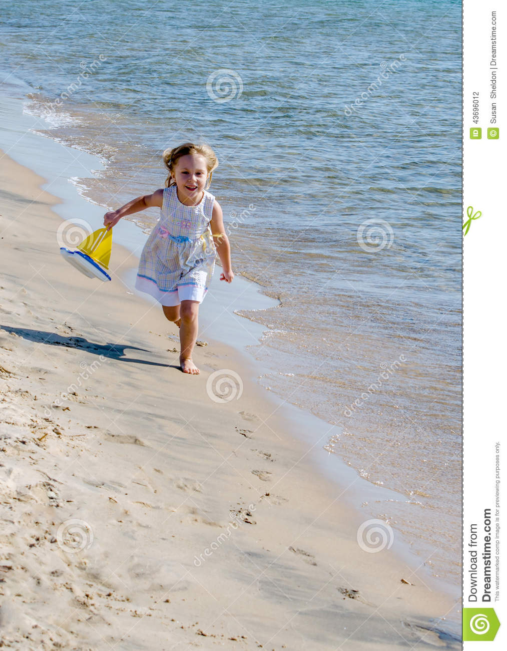 Happy child running on beach with toy boat