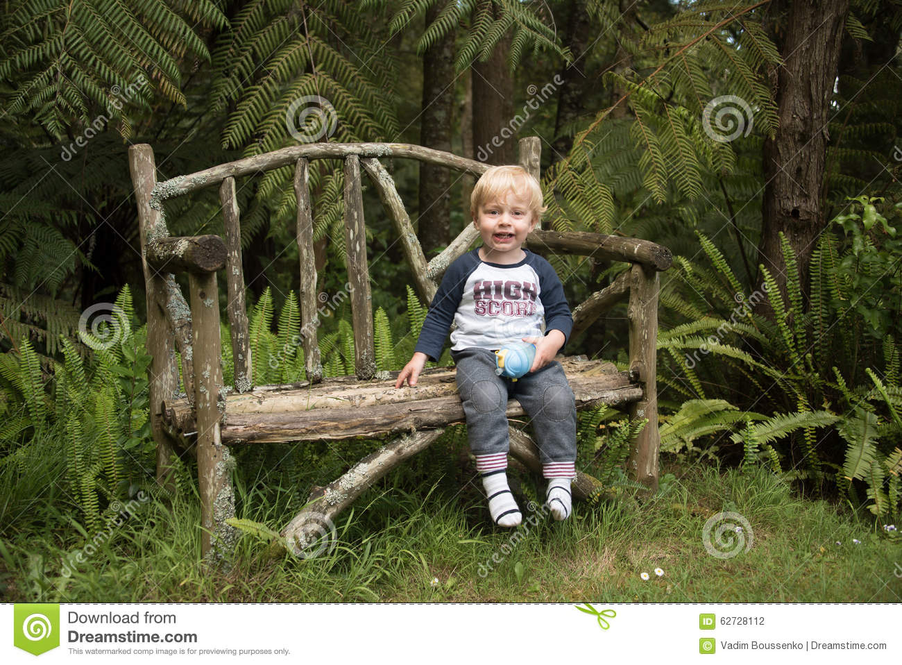 A Happy Child Sitting On A Garden Bench Stock Photo - Image of happy