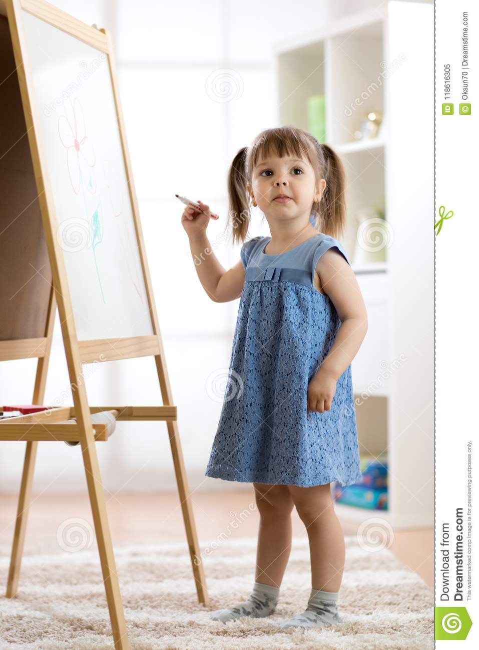 Happy cute toddler girl drawing or writting with marker pen on a blank whiteboard at home, preschool, daycare or
