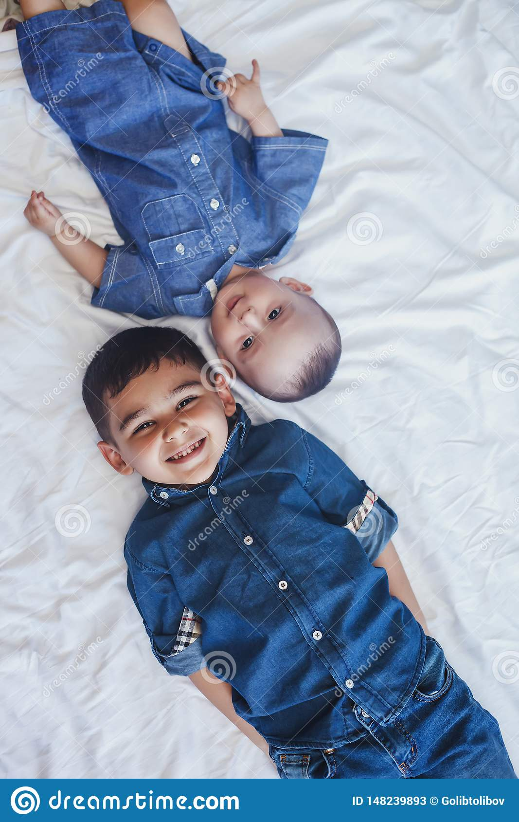 Happy childhood concept. Happy brothers portrait. 6 years boy and 6 months old baby boy having fun. Two little kids smiling to the