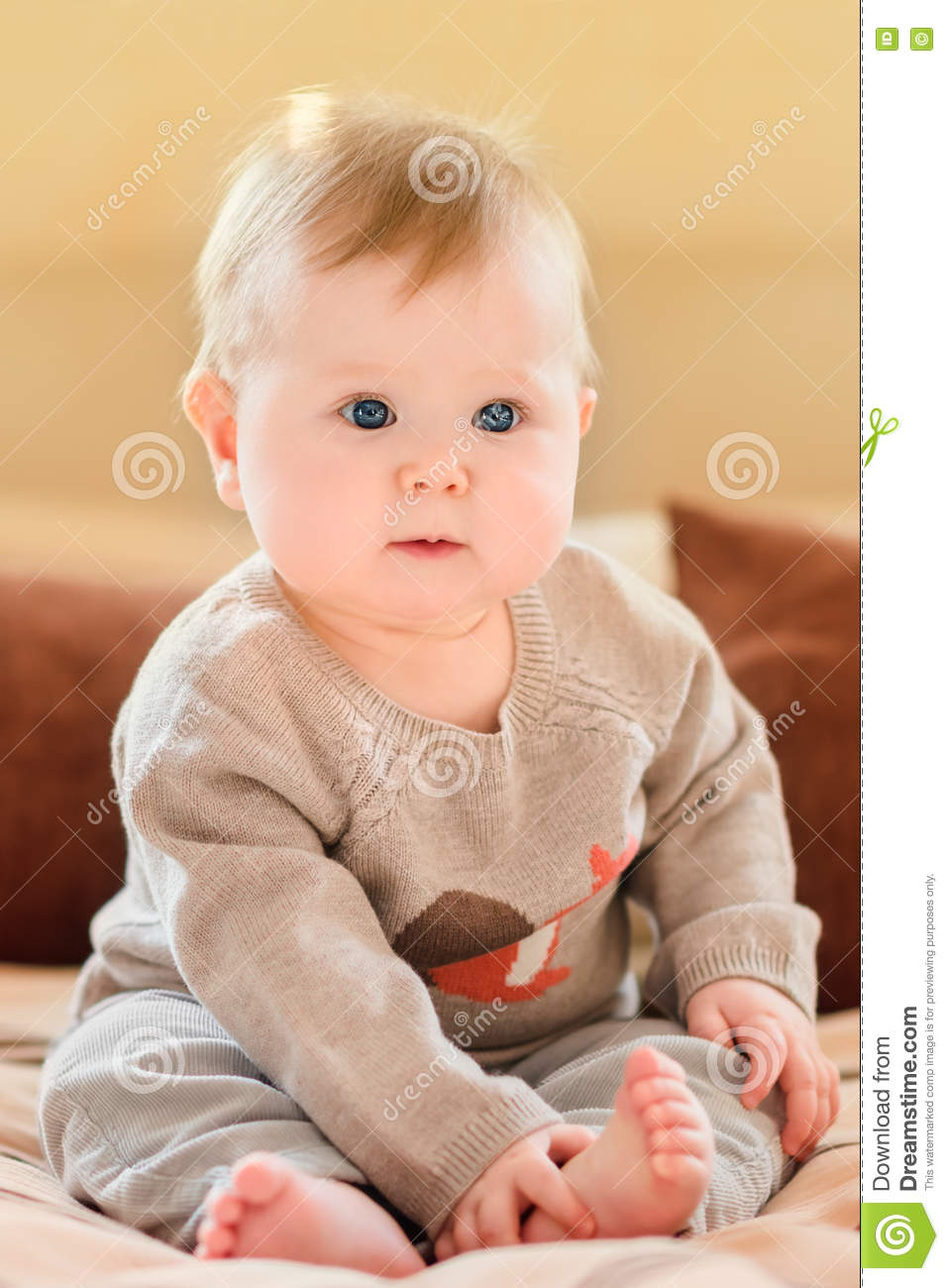 Happy childhood. Cute little child with blond hair and blue eyes wearing knitted sweater sitting on sofa and touching her leg