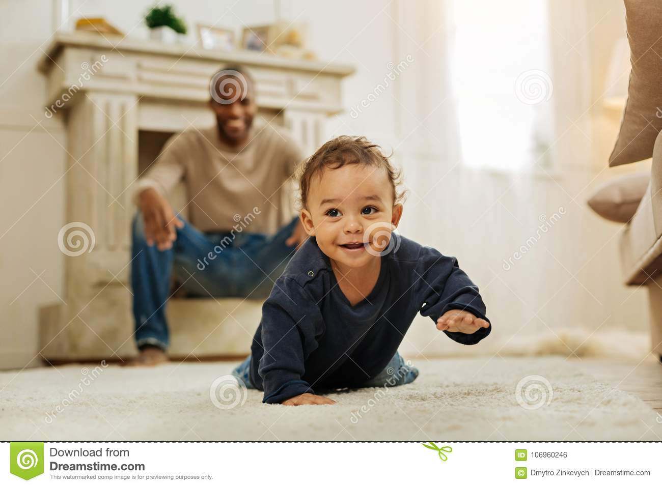 Smiling father watching his son crawling