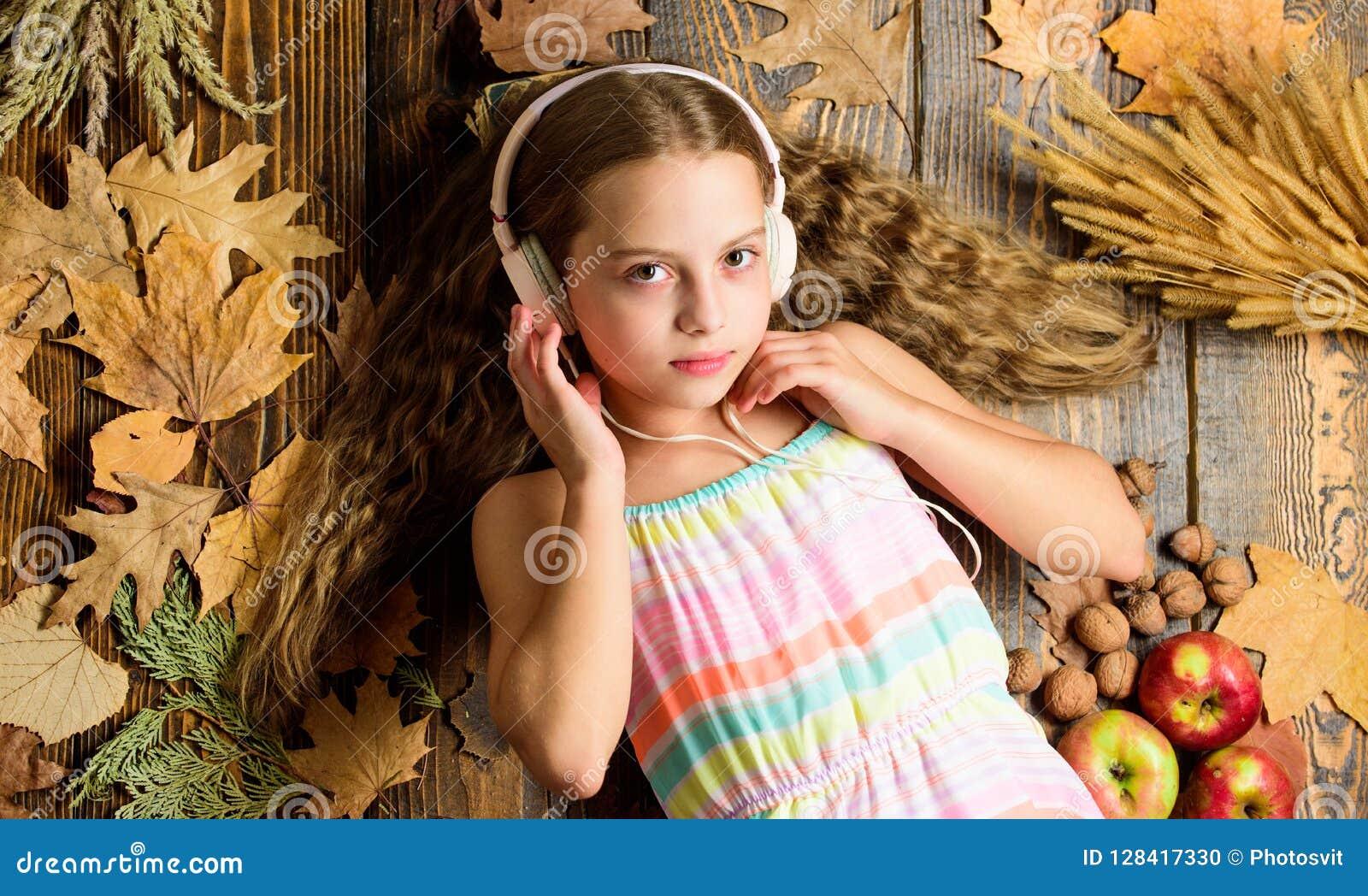Kid girl wooden background listen music headphones autumn melody concept child listen music relaxing top view autumn music playlist