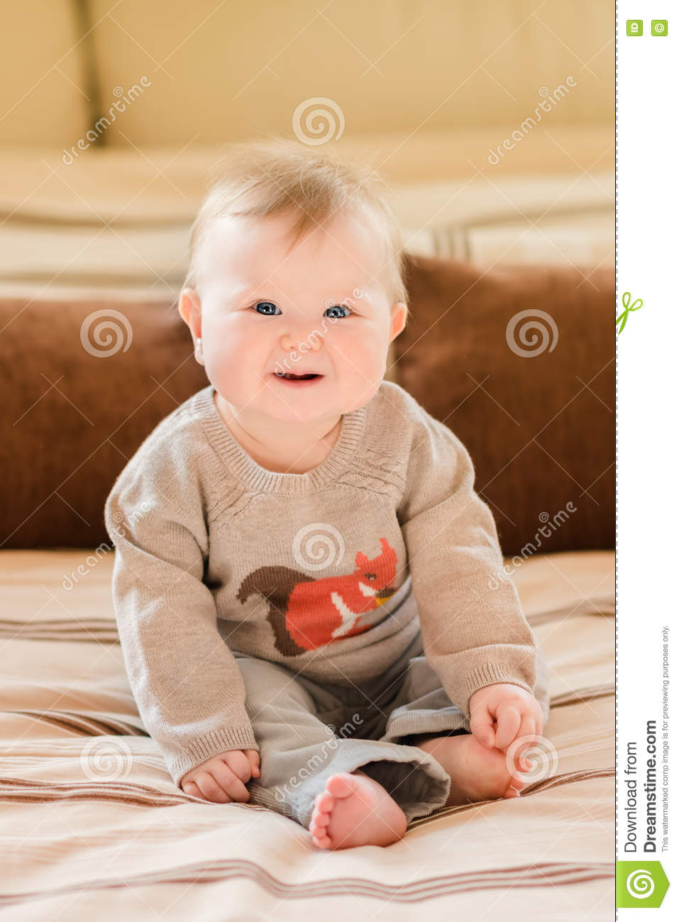 Happy childhood. Laughing little child with blond hair and blue eyes wearing knitted sweater sitting on sofa and touching her leg