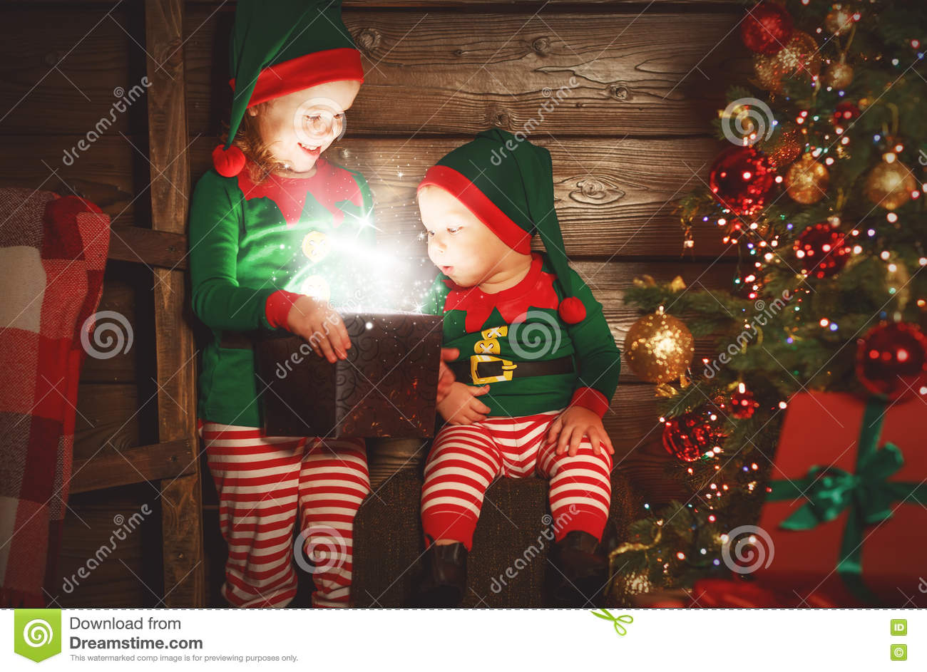 happy children brother and sister elf, helper of Santa with Christmas magic gifts