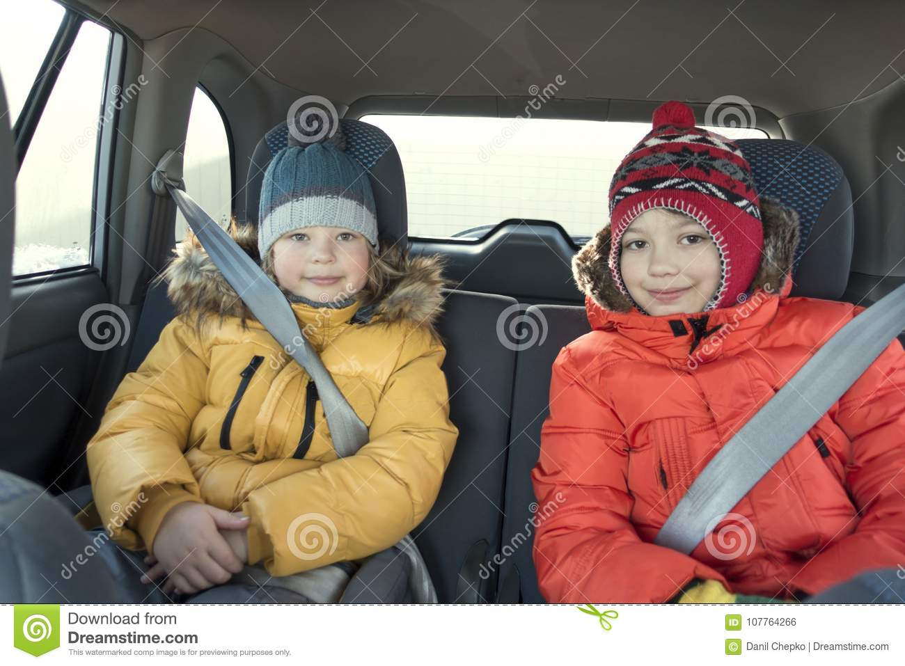 Happy children in the car in the back seat winter trip