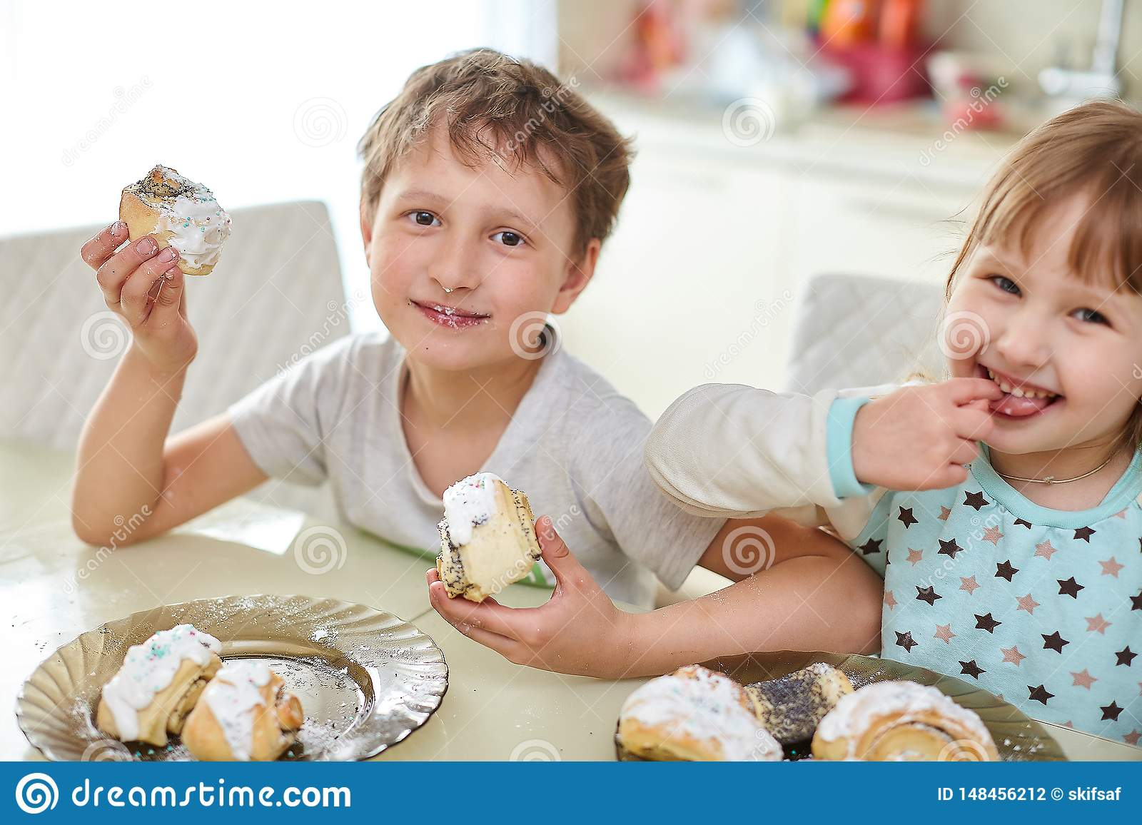 Happy children eat pastries in the bright kitchen at the table