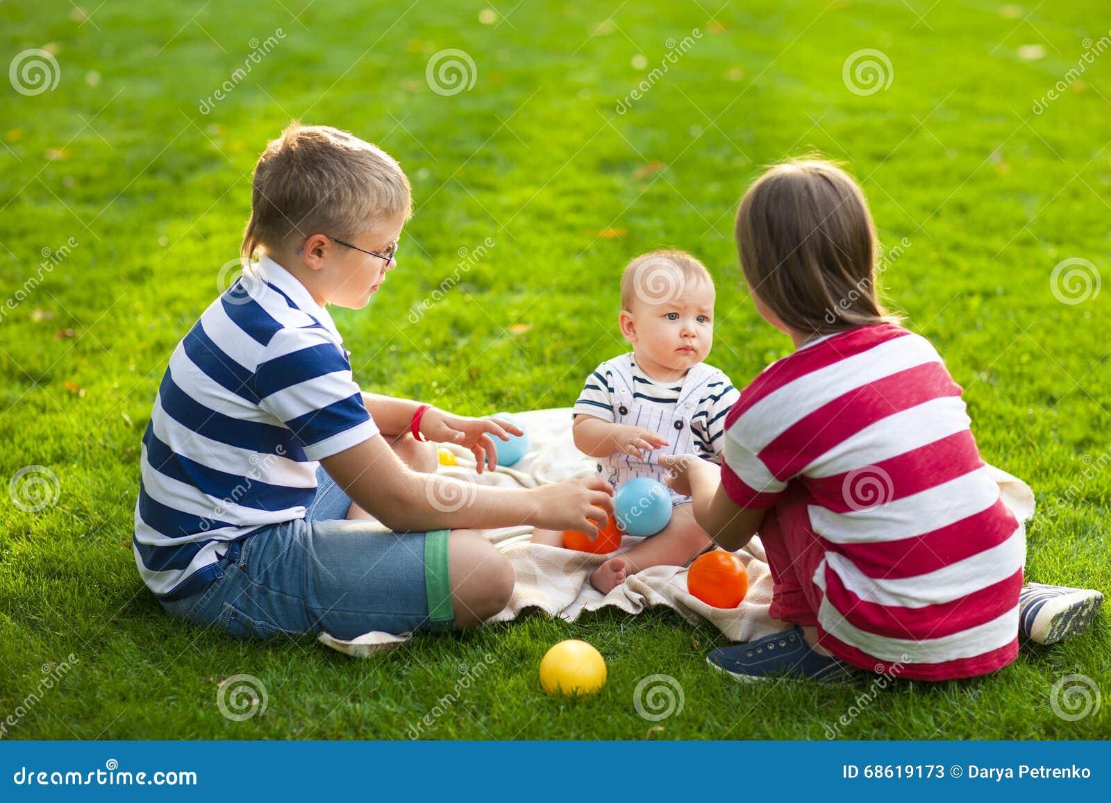 Happy children on green grass in summer park. Healthy lifestyles