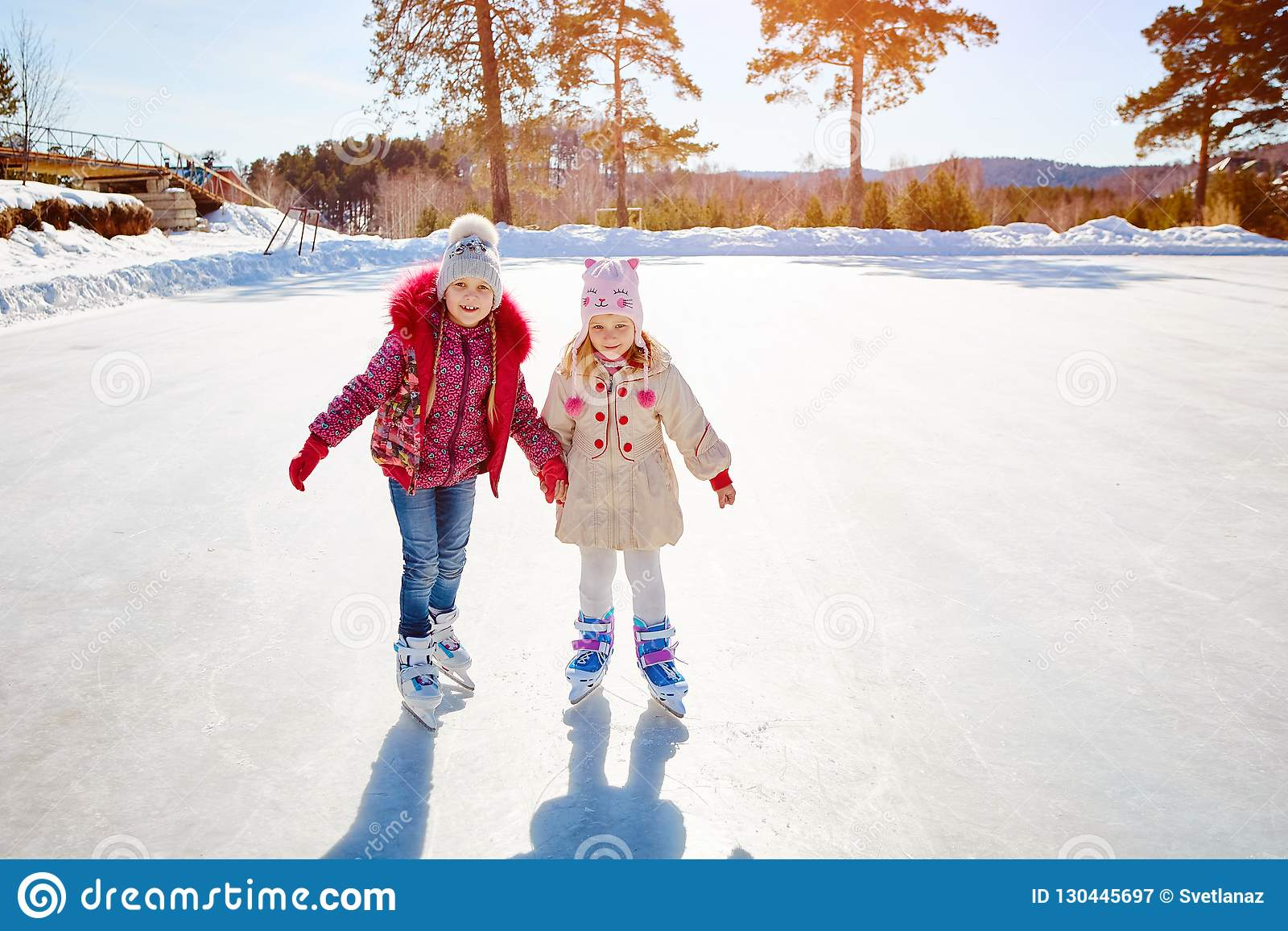 Happy children ice skating on an ice rink outdoors. Sport and a healthy lifestyle. Funny kids, they are sisters and girlfriends