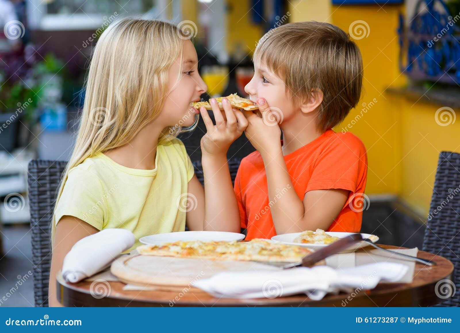 Happy Children Indoors Eating Pizza Smiling Stock Photo