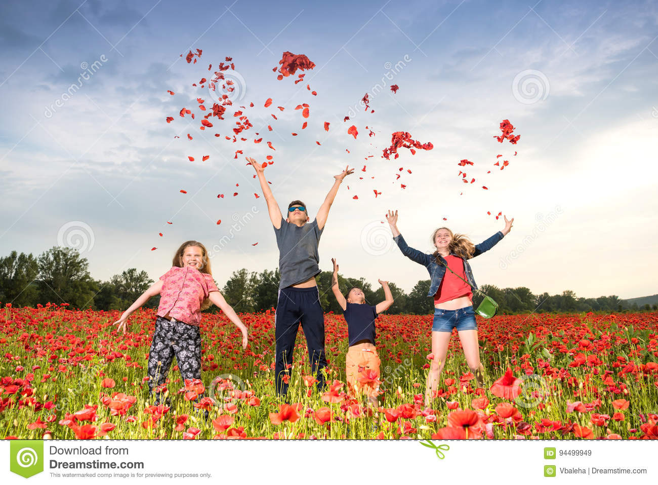 Happy children jumping and throwing petals of poppies