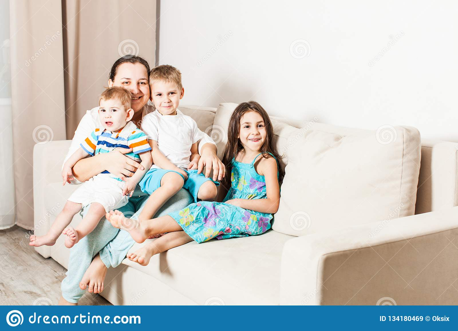 Happy children with mom are sitting on the sofa.