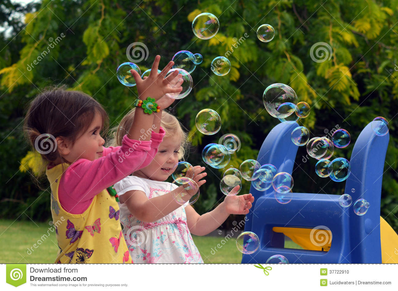 Happy Children Play With Soap Bubbles Stock Photo