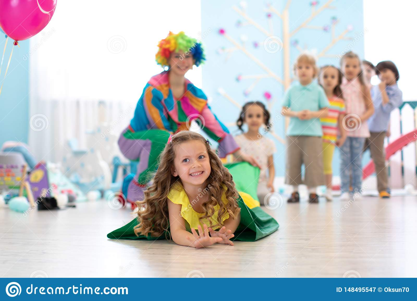 Happy children playing in childrens playroom for birthday party or entertainment centre. Kids amusement park and play