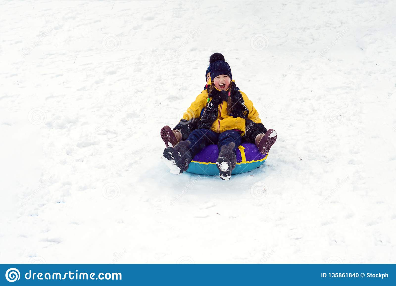 Happy children sledding tubing. brother and sister play together in winter. children slide down the hill. kids laugh and scream