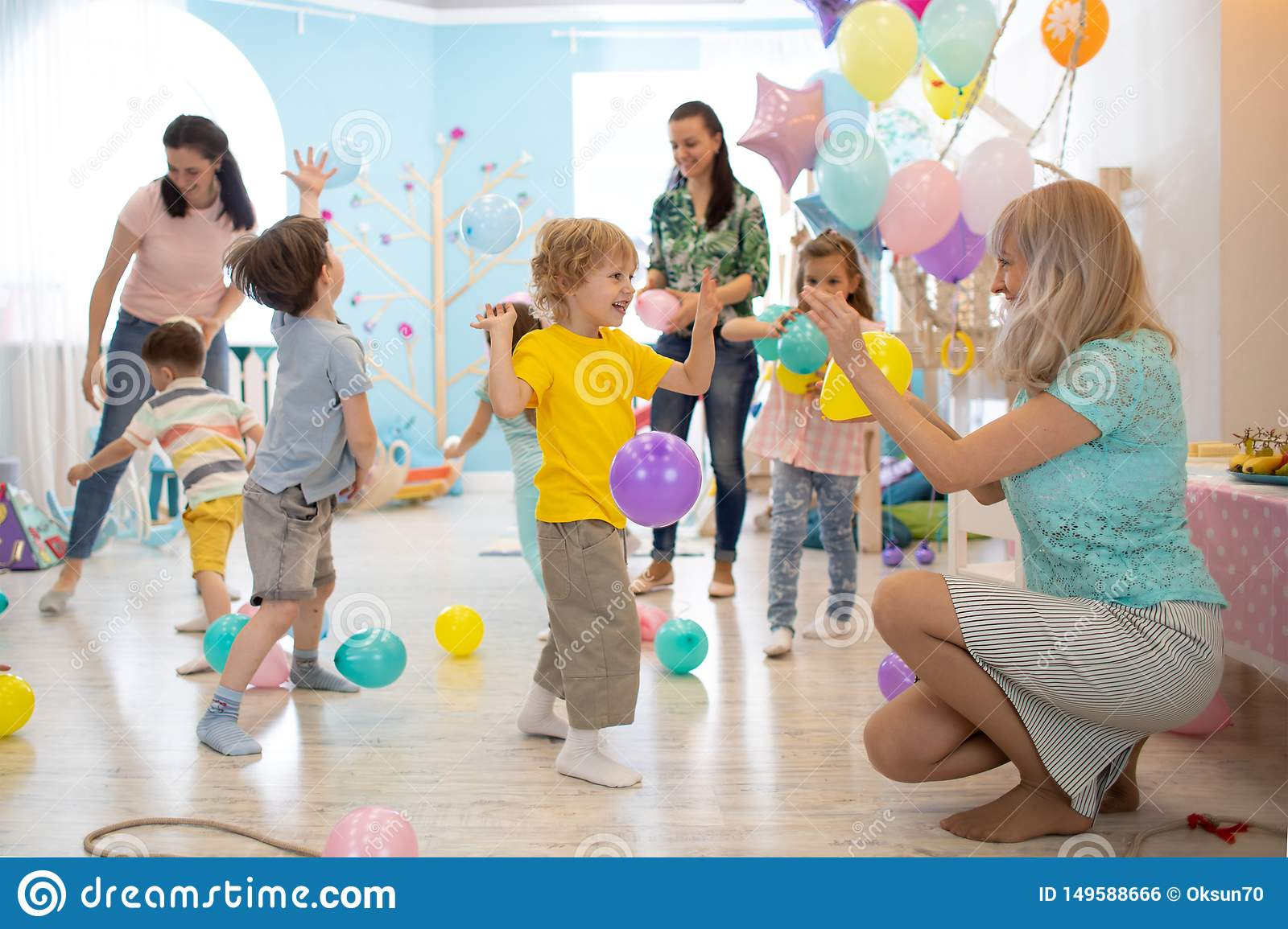 Joyful kids and their parents entertain and have fun with color balloon on birthday party