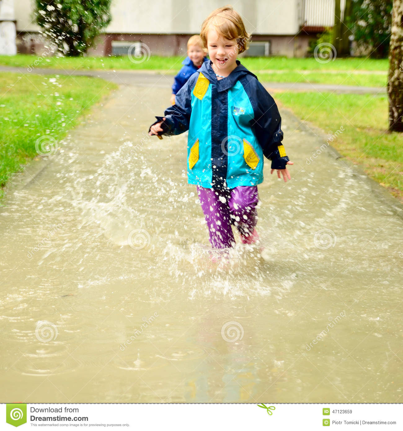 Happy Children In Water Proof Clothes Running Through The
