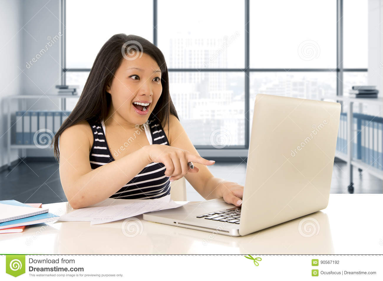 Happy chinese asian woman working and studying on her computer sitting at modern office desk smiling cheerful