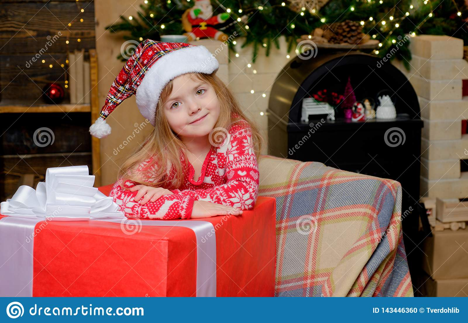 Happy Christmas little girl is looking at the camera with a big Christmas present. Beautiful little girl wearing Santa
