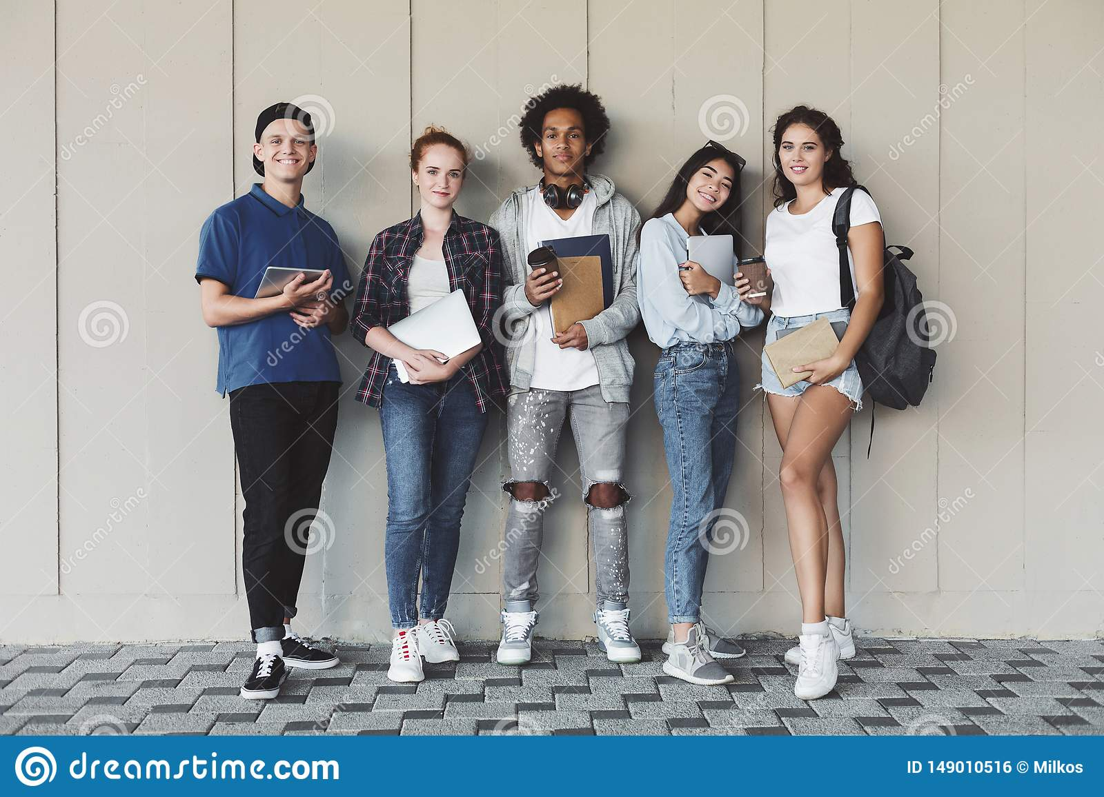 Happy college students posing with studying staff at campus wall