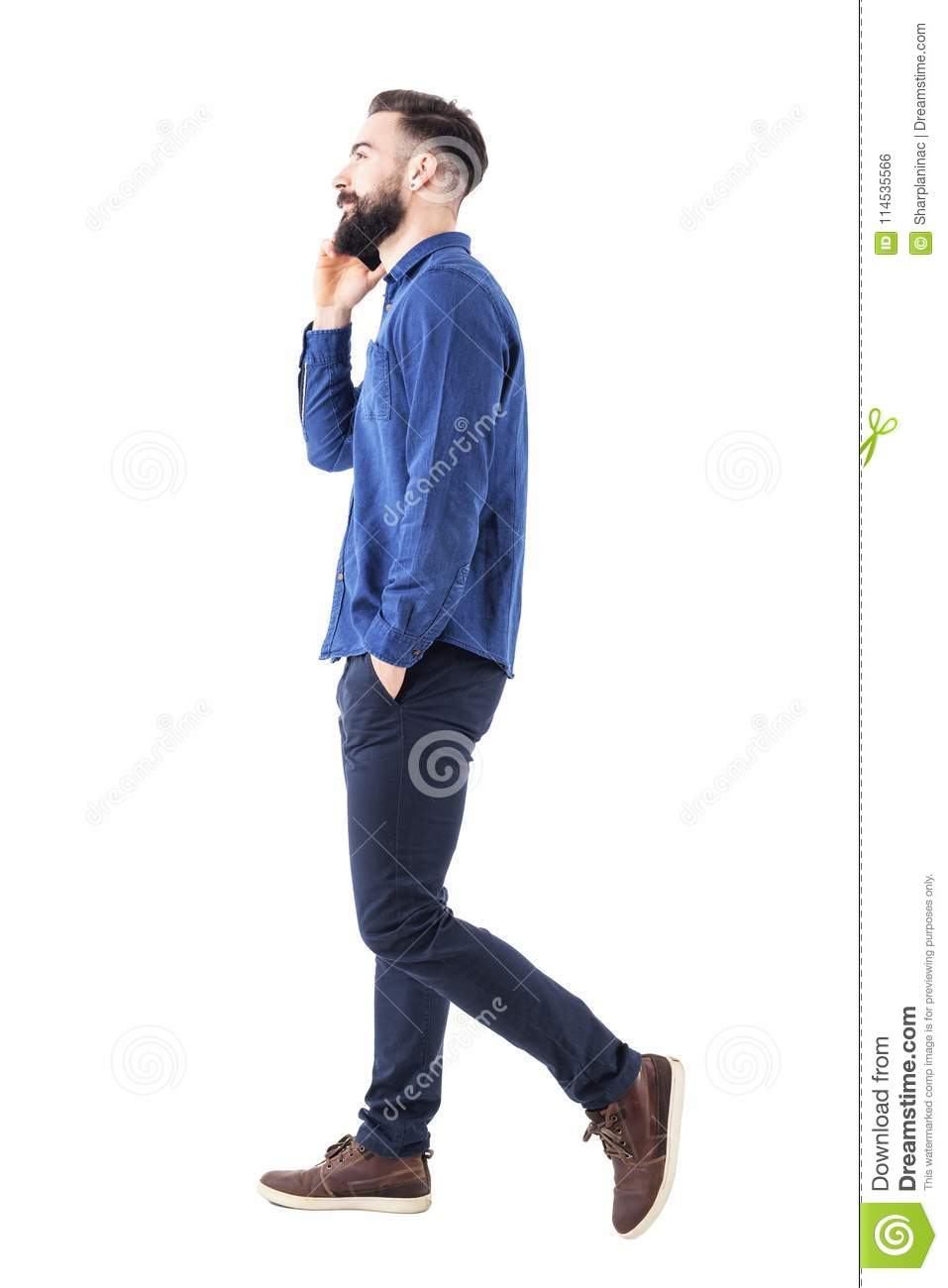 Happy confident successful business man walking and talking on cell phone with hands in pockets looking up