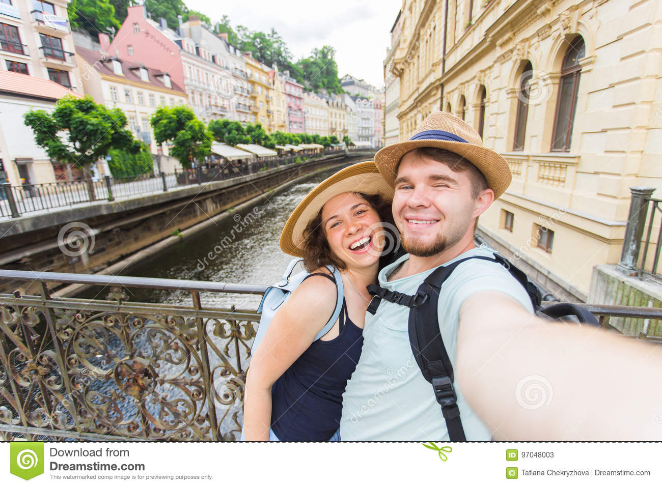Happy couple, attractive woman and man walking in city and enjoying romance. Lovers making selfie and smiling. Tourists