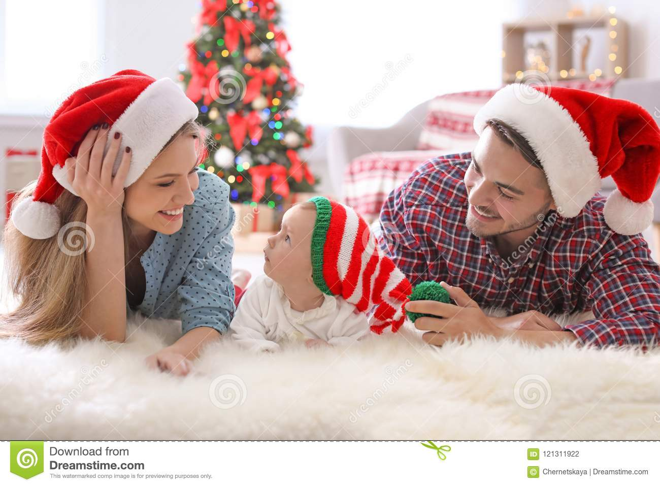 Happy couple with baby in Christmas hats