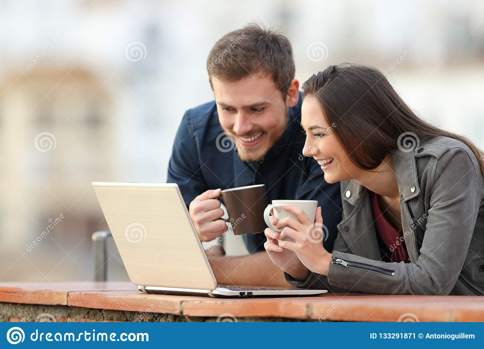 Happy couple checking laptop content on a balcony