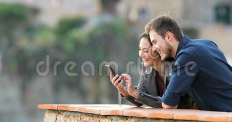 Happy couple checking phone content in a balcony. Happy couple checking smart phone content in a rural apartment balcony stock video