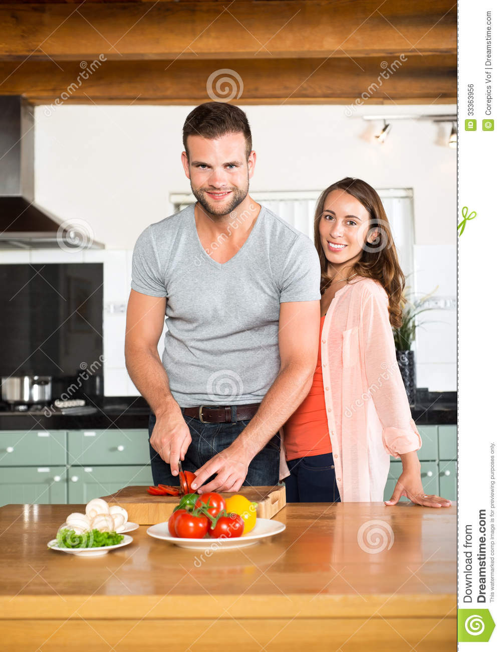 Happy Couple Chopping Vegetables At Kitchen Counter
