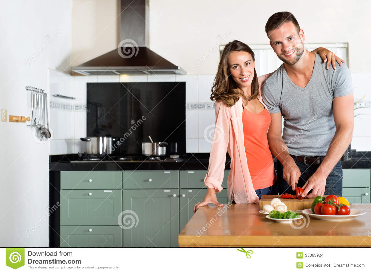 Happy Couple Cutting Vegetables At Kitchen Counter