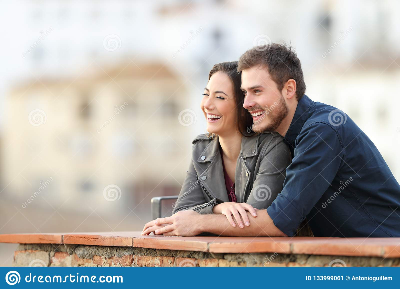 Happy couple enjoying views in a terrace on vacation