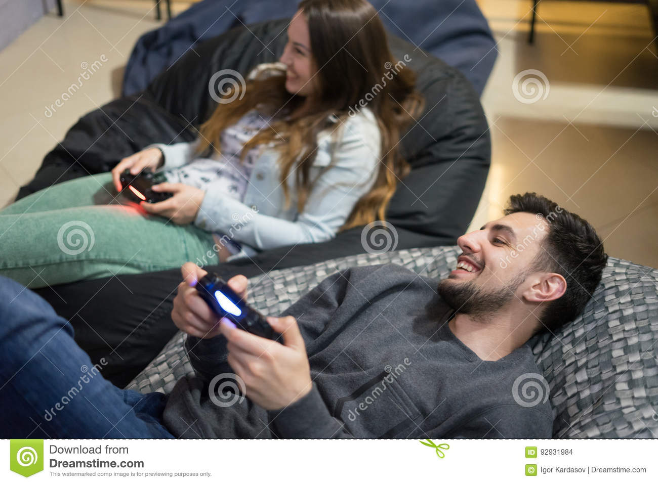 Happy Couple Friends Playing Video Games With Joystick Sitting On